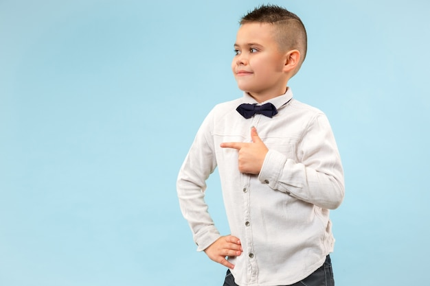 Szczęśliwy chłopiec nastolatka stojąc i uśmiechając się na niebieskim tle.