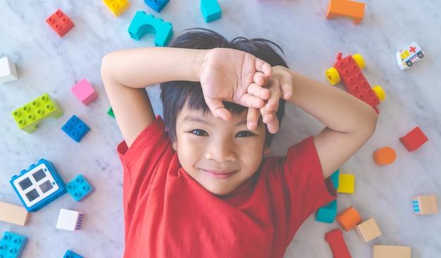Szczęśliwy chłopiec otoczony kolorowe klocki zabawki