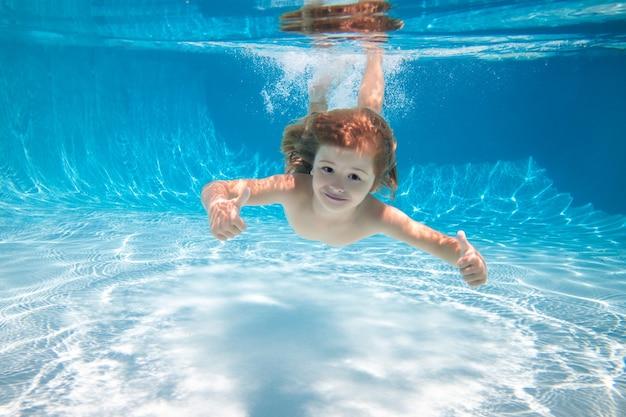 Szczęśliwy chłopiec pływanie i nurkowanie pod wodą dzieciak z zabawą w basenie aktywny zdrowy styl życia sporty wodne unde...