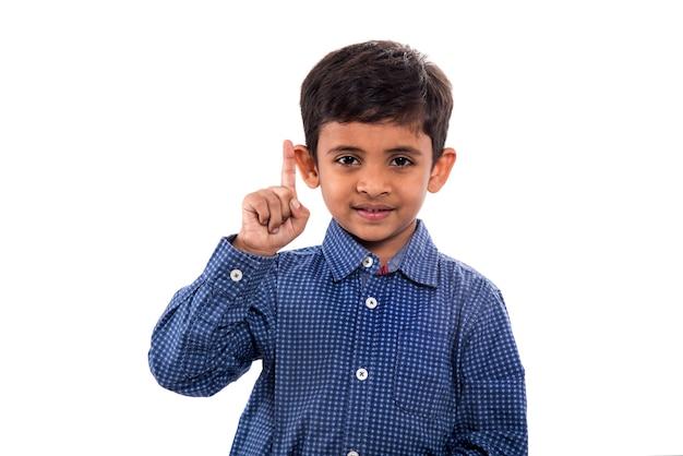Szczęśliwy chłopiec pokazuje kciuki do góry i palec na białym tle