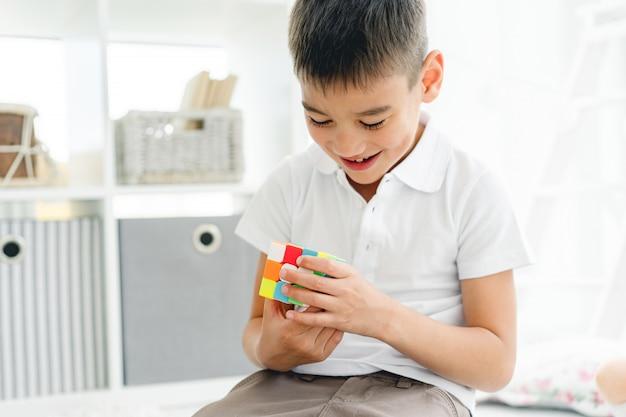 Szczęśliwy chłopiec rozwiązywania kostki rubika