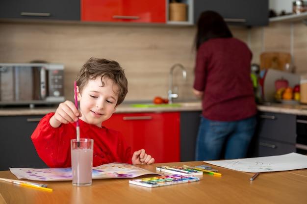 Szczęśliwy chłopiec rysuje obraz w kuchni z mamą