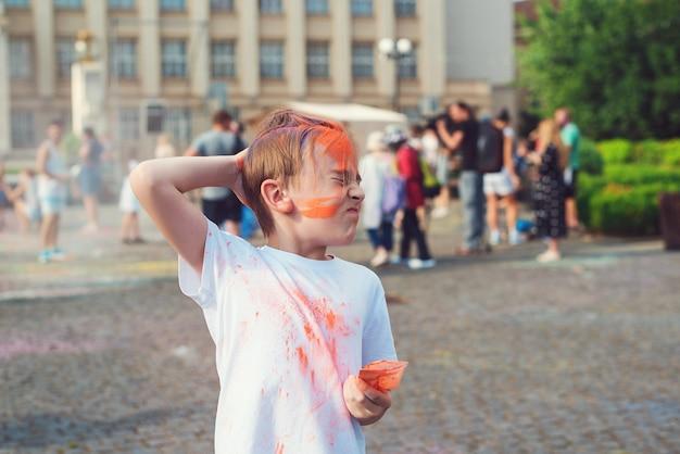 Szczęśliwy chłopiec rzucanie kolorowym proszkiem. koncepcja indyjskiego festiwalu holi. śliczny chłopiec pomalowany w barwach festiwalu holi. szczęśliwe dzieciństwo. święto holi.