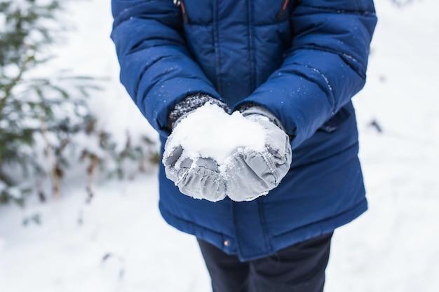 Szczęśliwy chłopiec rzucanie śniegiem