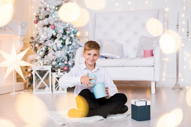 Szczęśliwy chłopiec siedzący na podłodze otwiera prezent w jasnej atmosferze świątecznej atmosfery