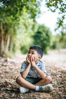 Szczęśliwy chłopiec siedzi i myśleć samotnie w parku