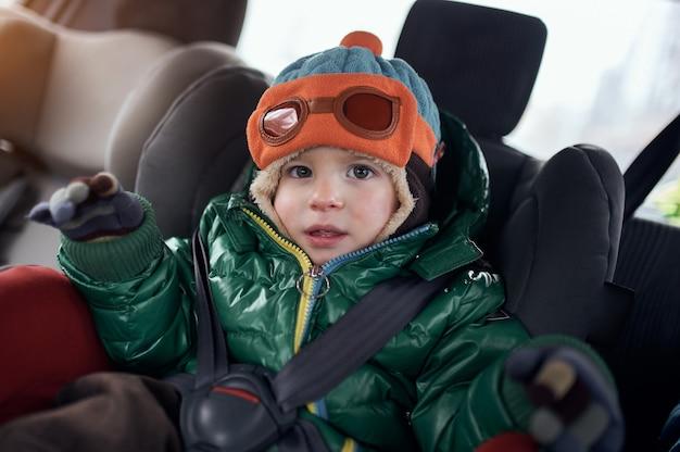 Szczęśliwy chłopiec siedzi w foteliku samochodowym dla dzieci.