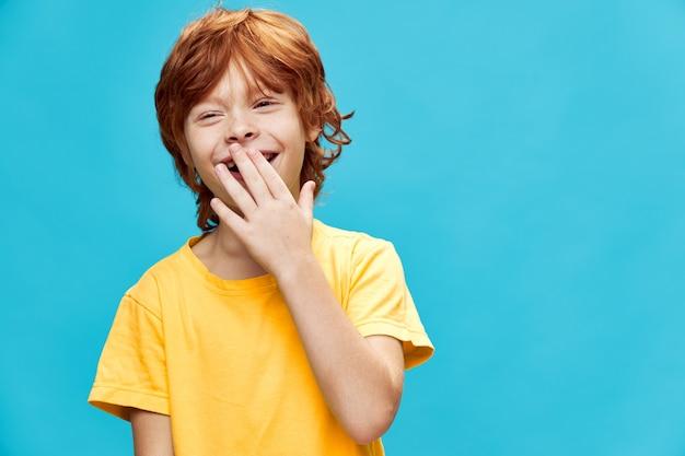 Szczęśliwy chłopiec śmiejąc się, zasłaniając usta ręką na niebiesko żółtej koszulce