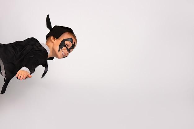 Szczęśliwy chłopiec superbohatera w czarnym stroju nietoperza z kapeluszem i uszami latającymi jak błyskawica na niebie.