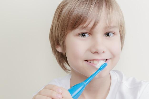 Szczęśliwy chłopiec szczotkuje zęby elektryczną szczoteczką do zębów