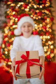 Szczęśliwy chłopiec trzyma pudełko z prezentem na wakacje adwentowe