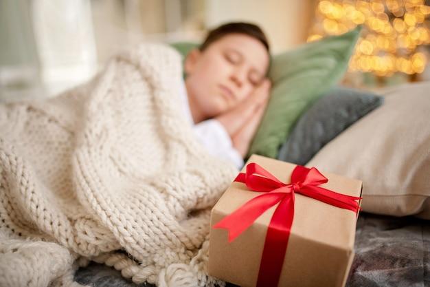 Szczęśliwy chłopiec trzyma pudełko z prezentem
