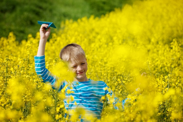 Szczęśliwy chłopiec trzyma w ręku niebieski papierowy samolot w jasny słoneczny dzień w żółtym polu fowers