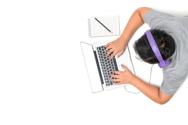 Szczęśliwy chłopiec uczeń bawić się komputer z zestawami słuchawkowymi i cieszy się naukę online