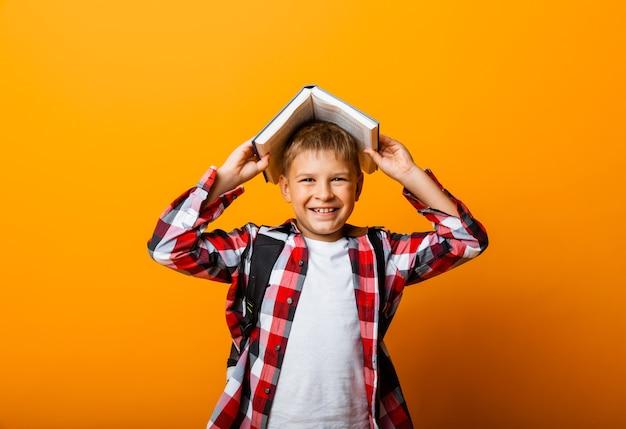 Szczęśliwy chłopiec uśmiechający się do kamery i trzymający książki na głowie, na żółtym tle