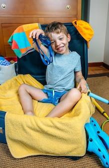 Szczęśliwy chłopiec uśmiechający się siedzący w walizce gotowy do wyjazdu na wakacje pokazujący okulary do pływania