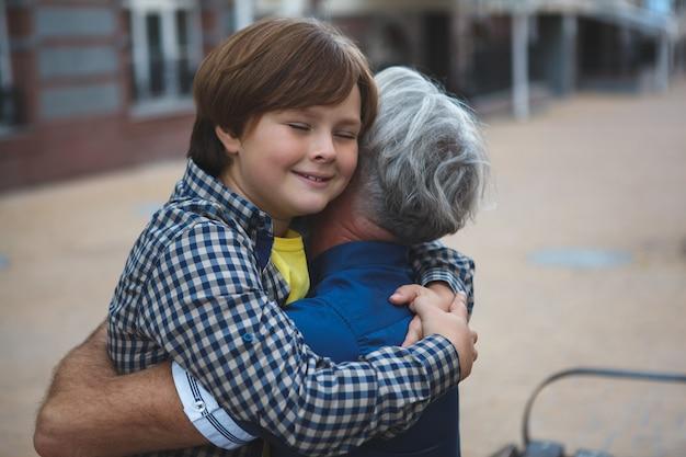 Szczęśliwy chłopiec uśmiechnięty z zamkniętymi oczami przytulanie swojego dziadka