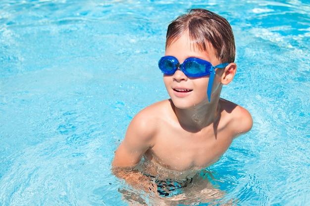 Szczęśliwy chłopiec w basenie. ładny mały chłopiec, zabawy w basenie. na dworze. zajęcia sportowe dla dzieci.