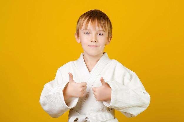 Szczęśliwy chłopiec w białym kimonie ćwiczy judo.