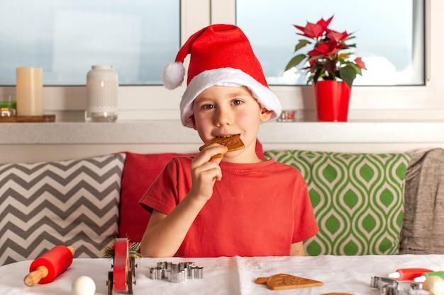 Szczęśliwy chłopiec w czapce świętego mikołaja jedzący świąteczne pierniki gotujące noworoczne pierniki