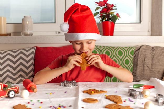 Szczęśliwy chłopiec w czapce świętego mikołaja, jedzenie świąteczne pierniki
