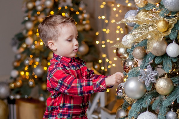 Szczęśliwy chłopiec w eleganckim świątecznym garniturze zdobi piękną choinkę w domu. wesołych świąt i szczęśliwego nowego roku
