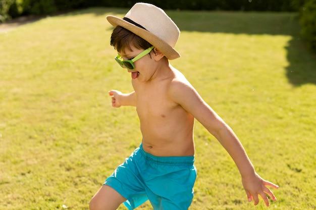 Szczęśliwy chłopiec w kapeluszu i okulary przeciwsłoneczne