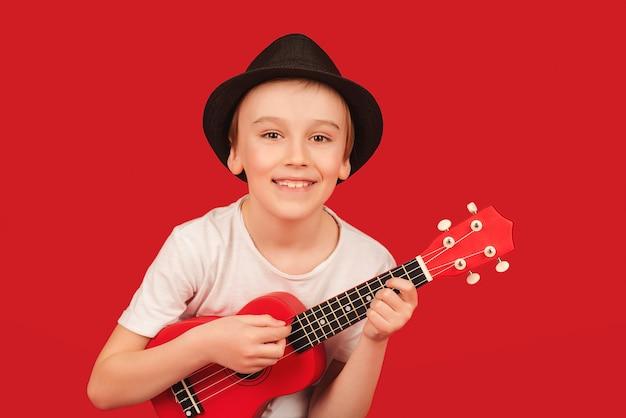 Szczęśliwy chłopiec w letnim kapeluszu grający na ukulele mały chłopiec z hawajską gitarą bawi się szczęśliwy dzieciak
