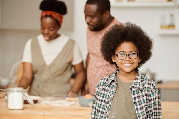 Szczęśliwy chłopiec w okularach uśmiechający się do gotowania swoich rodziców