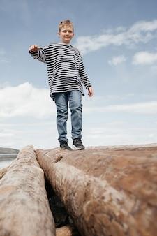 Szczęśliwy chłopiec w pasiastej kamizelce idzie wzdłuż polan do brzegu. chłopiec stara się zachować równowagę, przechadzając się po kłodach. weekendowy odpoczynek.
