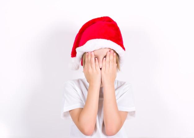 Szczęśliwy chłopiec w santa czerwony kapelusz overing jego twarz rękami. koncepcja na boże narodzenie