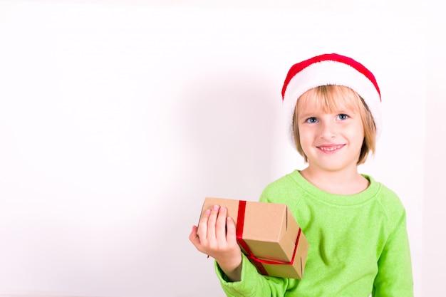 Szczęśliwy chłopiec w santa czerwony kapelusz trzymając w ręku prezent na boże narodzenie. copyspace