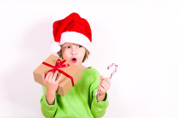 Szczęśliwy chłopiec w santa czerwony kapelusz trzymając w ręku prezent na boże narodzenie. koncepcja bożego narodzenia.