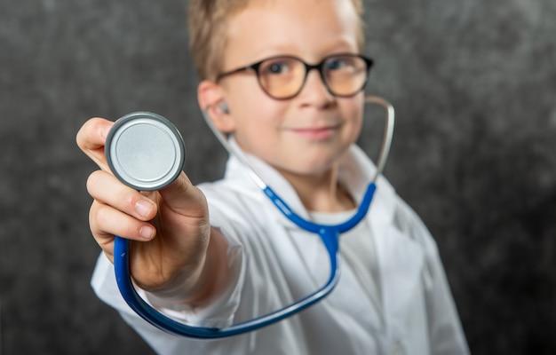 Szczęśliwy chłopiec w stroju lekarz trzymając kostium