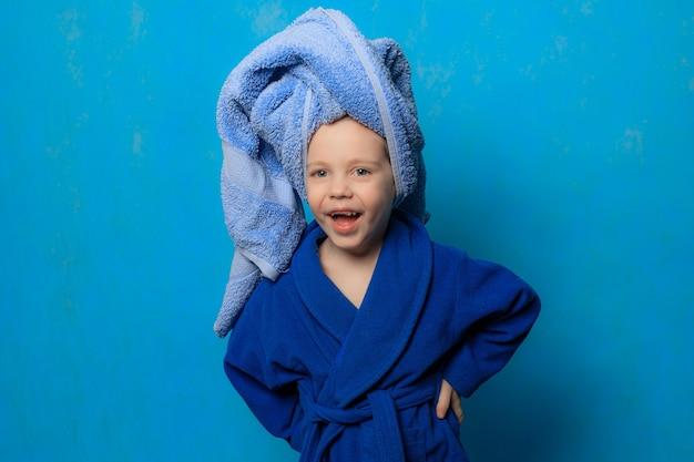 Szczęśliwy chłopiec w szlafroku i ręczniku wokół głowy na niebieskim tle