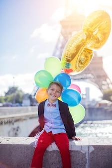 Szczęśliwy chłopiec z bukietem kolorowych balonów w paryżu, w pobliżu wieży eiffla.