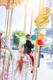 Szczęśliwy chłopiec z pękiem kolorowych balonów bawiących się na karuzeli w paryżu.