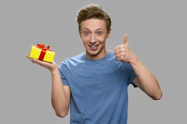 Szczęśliwy chłopiec z pudełko pokazując kciuk do góry. młody mężczyzna trzyma pudełko i gestykuluje kciuk przeciw szaremu tłu.