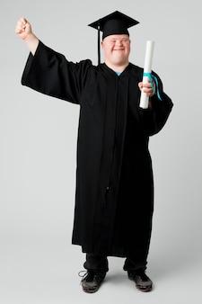 Szczęśliwy chłopiec z zespołem downa w sukni na zakończenie szkoły