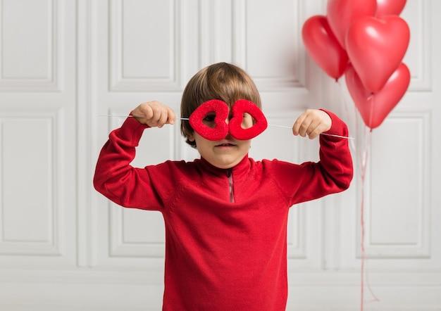 Szczęśliwy chłopiec zamknął oczy dwoma sercami na białym tle z balonami sercami