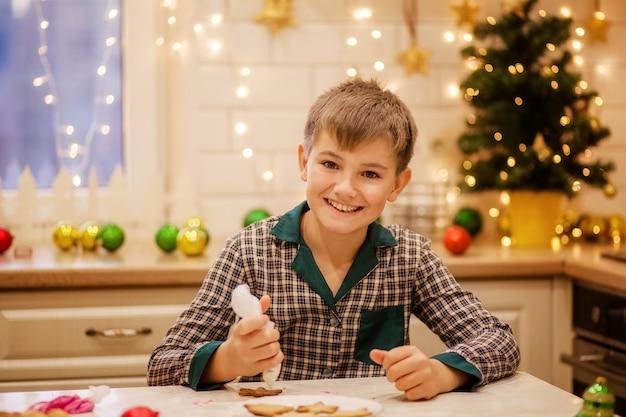 Szczęśliwy chłopiec zrobić imbirowe świąteczne ciasteczka w domu w kuchni