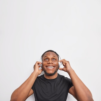 Szczęśliwy ciemnoskóry brodaty mężczyzna skupiony nad uśmiechami szeroko trzyma ręce na słuchawkach stereo