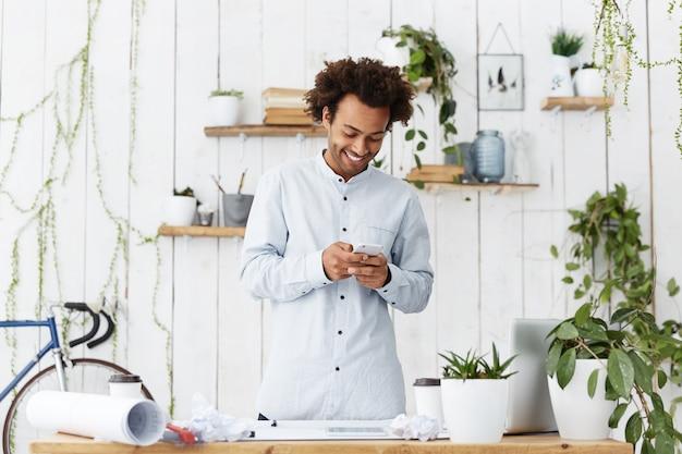 Szczęśliwy ciemnoskóry robotnik budowlany stojący w pobliżu swojego miejsca pracy, trzymając telefon komórkowy
