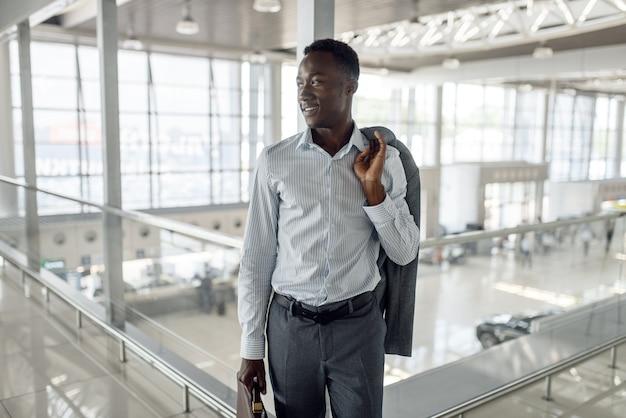 Szczęśliwy czarny biznesmen z teczką w salonie samochodowym. przedsiębiorca odnoszący sukcesy na targach motoryzacyjnych, murzyn w formalnym stroju, salon samochodowy