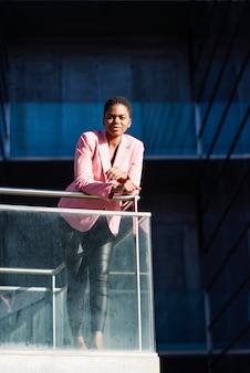 Szczęśliwy czarny bizneswoman stoi blisko biznesowego budynku biurowego.
