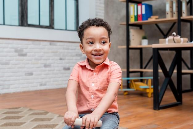 Szczęśliwy czarny chłopiec jedzie zabawkarskiego samochód