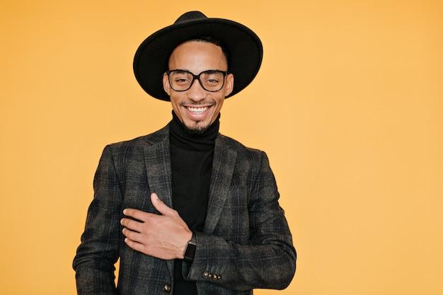 Szczęśliwy czarny młody człowiek nosi elegancki ciemny garnitur z zadowolonym uśmiechem. kryty zdjęcie zrelaksowanego modelu mulata w okularach podczas sesji zdjęciowej.