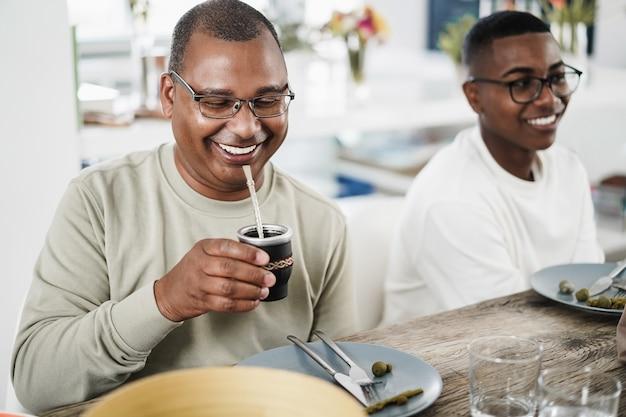 Szczęśliwy czarny ojciec pijący yerba mate podczas obiadu w domu - główny nacisk na twarz mężczyzny
