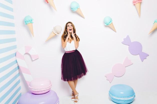 Szczęśliwy czas radosnej młodej kobiety w tiulowej spódnicy na białym tle wśród słodyczy. pastelowe kolory, makaroniki, lody, szczęście, modny model, dobra zabawa.