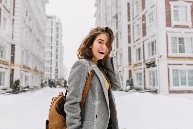 Szczęśliwy czas zimowy w wielkim mieście uroczej kobiety spaceru na ulicy w płaszczu z plecakiem. radość z opadów śniegu, wyrażanie pozytywności, uśmiech, radosny, wesoły nastrój, prawdziwe emocje, noworoczny nastrój.